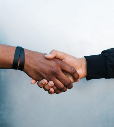 A close up image of two people shaking hands.